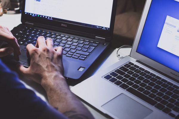 man working on 2 laptops