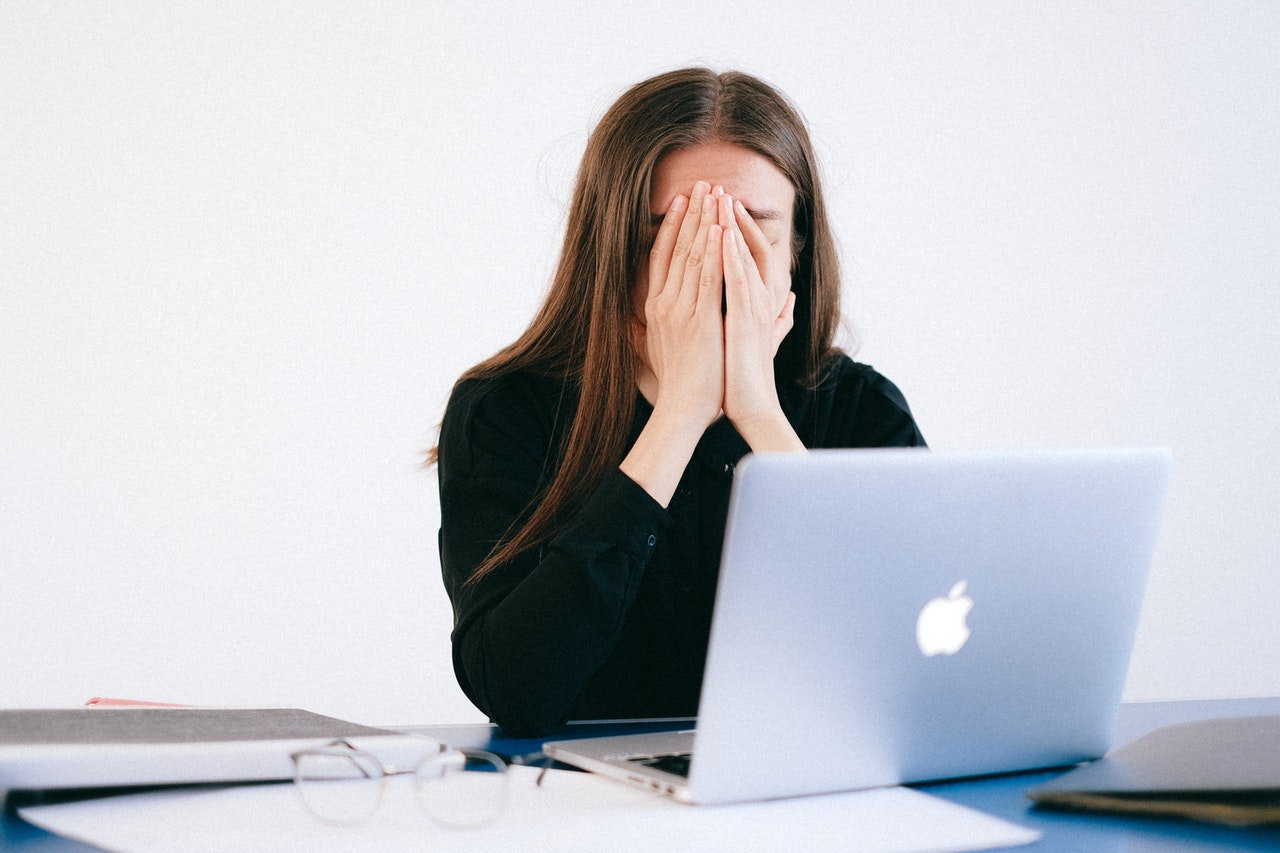 woman with head in hands at laptop